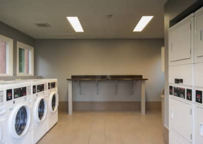 Laundry room with washers and dryers and bar to fold clothing