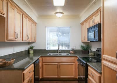 Kitchen with granite counters, maple cabinets, and black appliances