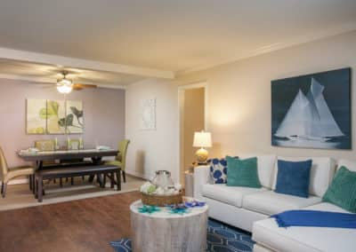 Whit couch with blue and green pillows in the Living area and long table with chairs and bench in the dining area. Nautical themed.