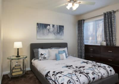 Bedroom with ceiling fan, grey headboard, white sheets with grey, white, and blue flowers printed on it, lamp on a glass table with books stacked on the lower part of the glass, modern piece of artwork above the bed and brown dresser to the right of the bed with a silver candle on top