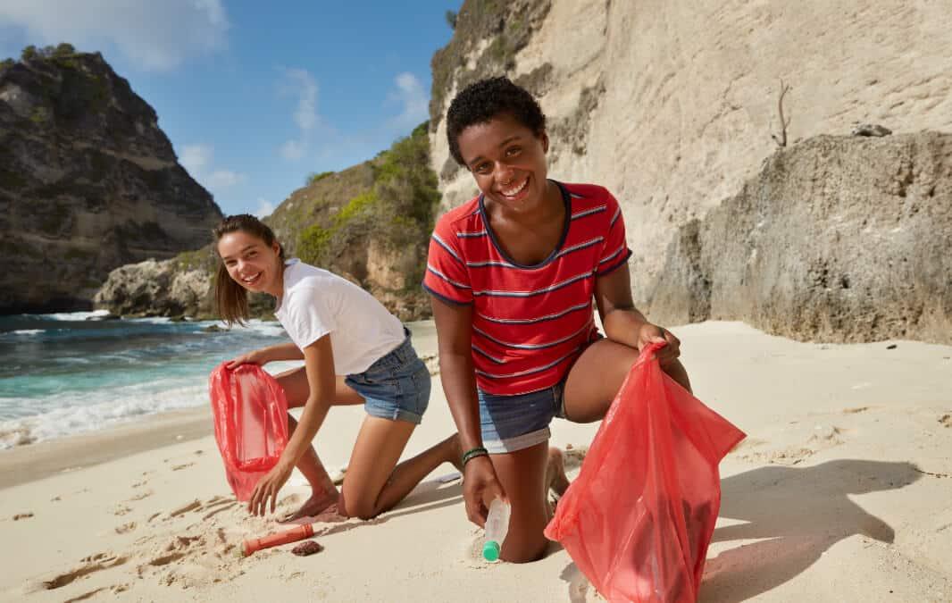 Two teens having a beach clean up